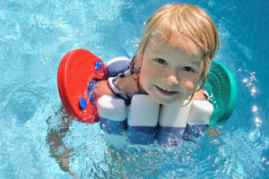 Kind geniesst den Pool mit Schwimmscheiben und Schwimmgurt