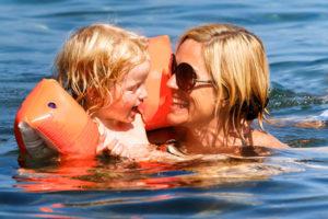 Mutter und Kind mit Schwimmflügel geniessen unbeschwert das Plantschen im Meer.
